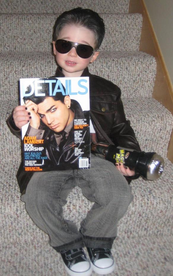 Kid dressed as Adam Lambert posing with Details magazine